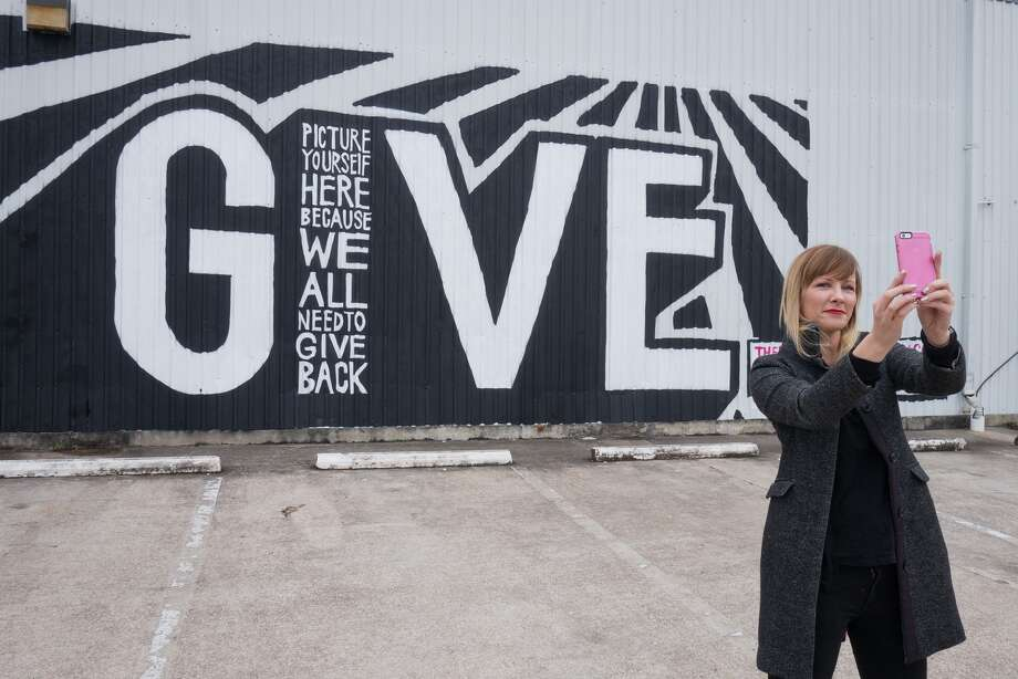 """Aimee Woodall, founder of the Black Sheep Agency hopes the """"Give"""" mural on Yale Street in the Heights will prompt people to reflect on how they can give back to the community and take photos of themselves in front of the work. """"The idea is that you put yourself into the picture, and you become the `I,'"""" she says. Photo: R. Clayton McKee, Freelance / © R. Clayton McKee"""