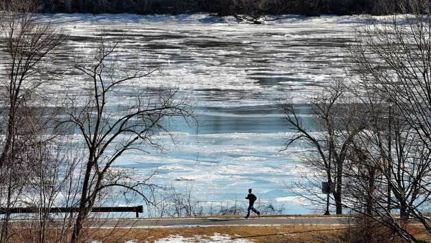 Ice covers most of the Hudson River as a runner makes his way along the bike path on Tuesday, Jan. 20, 2015, in Albany, N.Y.   (Paul Buckowski / Times Union) Photo: Paul Buckowski / 00030272A