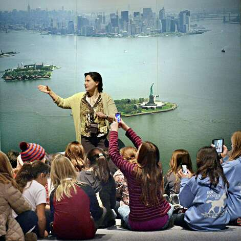 Museum educator Hatti Lansford, standing before a photo of New York harbor, recounts the history of Ellis Island to students from Lenapi Elementary School in New Paltz at the NYS Museum Tuesday Jan. 20, 2015 in Albany, NY.  (John Carl D'Annibale / Times Union) Photo: John Carl D'Annibale / 00030272A