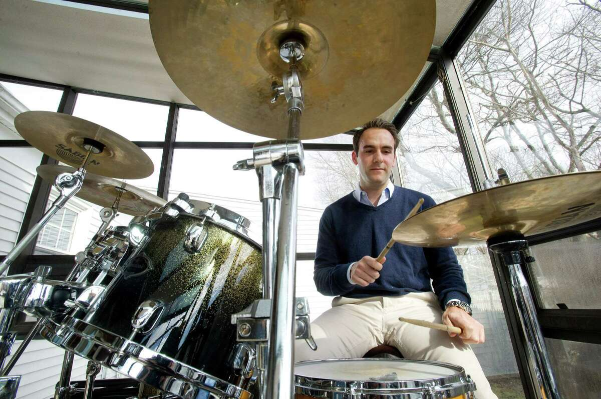 Adam Cognetta plays drums in the greenhouse in his Stamford home on Tuesday, January 20, 2015. Cognetta said the greenhouse reminds him of his grandfather, who enjoyed gardening and spent a lot of time in the room.
