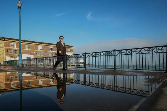 David Snyder walks past a puddle caused by king tides on Pier 14, Tuesday, Jan. 20, 2015, in San Francisco, Calif. Snyder came down to see the tides during a break from work.