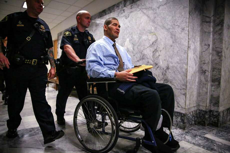 "Christopher Monfort is wheeled from court as he says, ""hands up, don't shoot,"" to gathered spectators in a hallway after opening arguments in his trial for the 2009 killing of Seattle Police Officer Timothy Brenton. Monfort is also accused of attempted murder, arson and a host of other crimes. He was paralyzed after being shot by police when he pulled a gun on a detective investigating the crime. Photographed on Tuesday, January 20, 2015 at the King County Courthouse Photo: JOSHUA TRUJILLO, SEATTLEPI.COM / SEATTLEPI.COM"