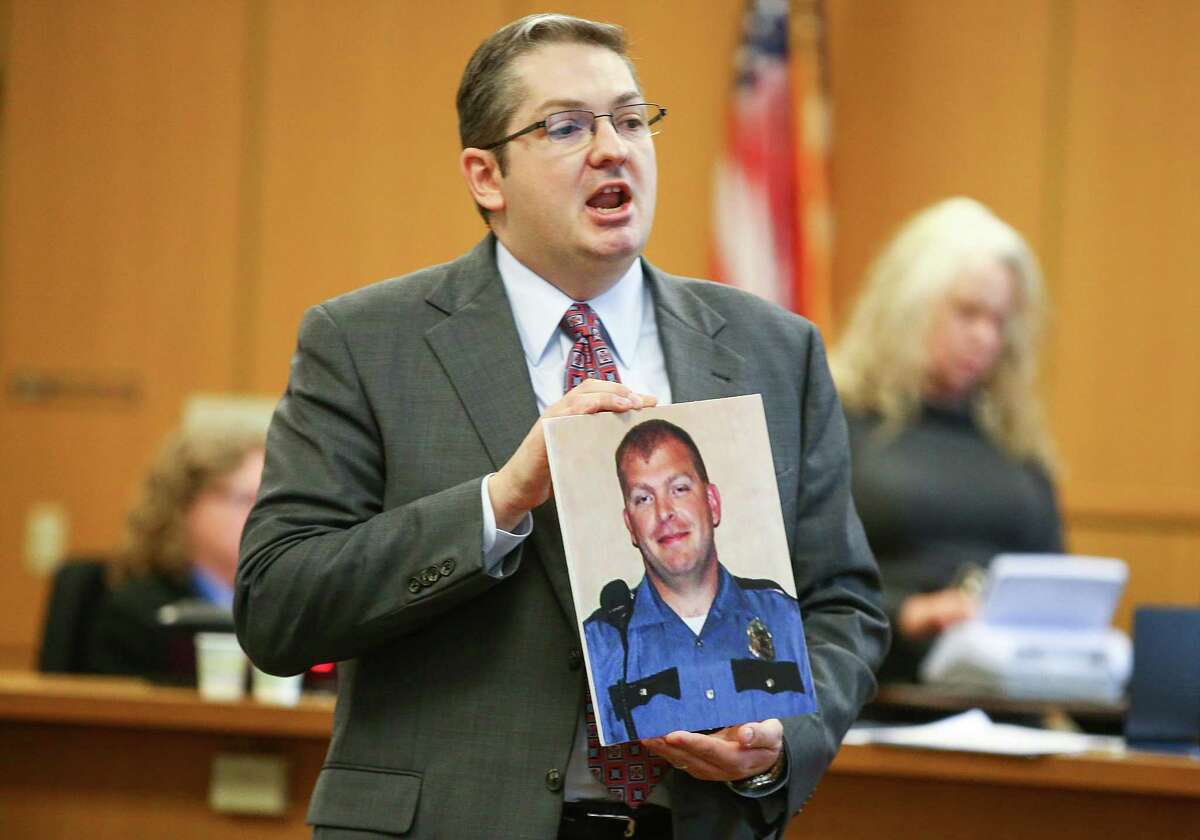 On Halloween 2009, Monfort opened fire into a stopped police cruiser. Seattle Police Department Officer Tim Brenton was killed in the shooting, which nearly claimed the life of Officer Britt Kelly. Prosecutors say Monfort planned that unprovoked ambush as part of a personal war on police. Above, King County Senior Deputy Prosecutor John Castleton addresses the jury while holding a photograph of Brenton during opening arguments.