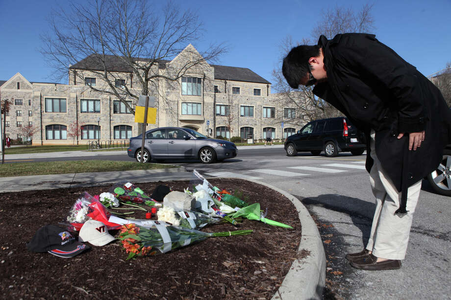 Xinghan Xu, a Virginia Tech student from China, bows at a makeshift memorial for Deriek Crouse, a campus police officer who was slain during a traffic stop in 2011. Photo: STEPHANIE KLEIN-DAVIS / Associated Press / THE ROANOKE TIMES