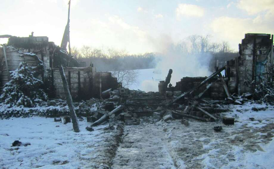 About 12 hours later, smoke still spews from the charred remnants of a the Diemer family home along Anderson Road in Sherman that was leveled Friday, Jan. 9,  2015 by an early-morning fire. Photo: Norm Cummings / The News-Times