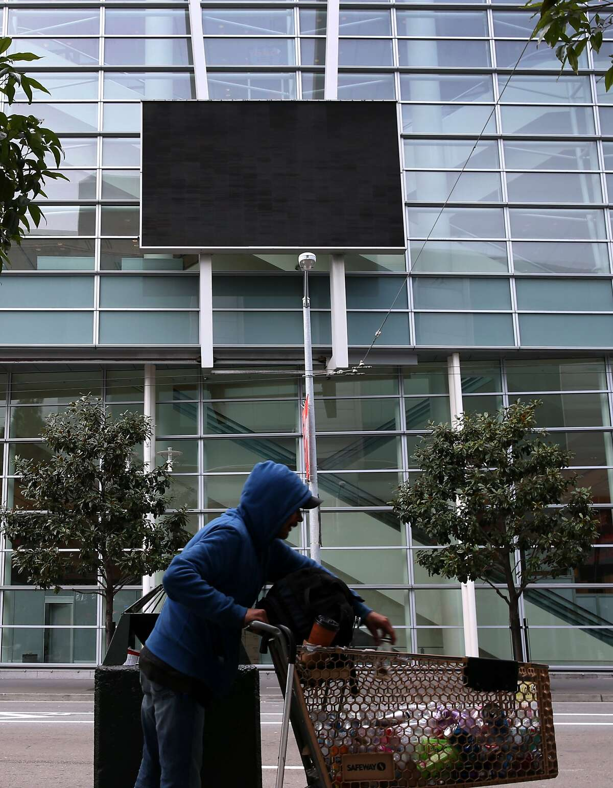 A man collects recyclables in front of a dark video screen installed on the side of Moscone West on Fourth Street in San Francisco, Calif. on Tuesday, Jan. 20, 2015. The screen has never really functioned since its installation in 2003.