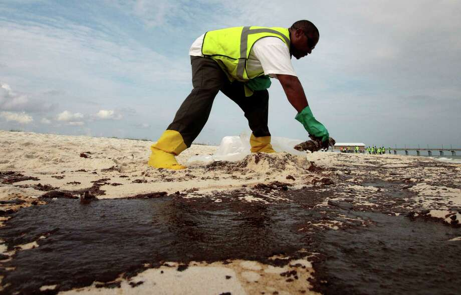 Steve Gardner scrapes oil from the sand in Gulf Shores, Ala., after the 2010 gulf oil spill. Photo: Dave Martin / Associated Press / FR159046 AP