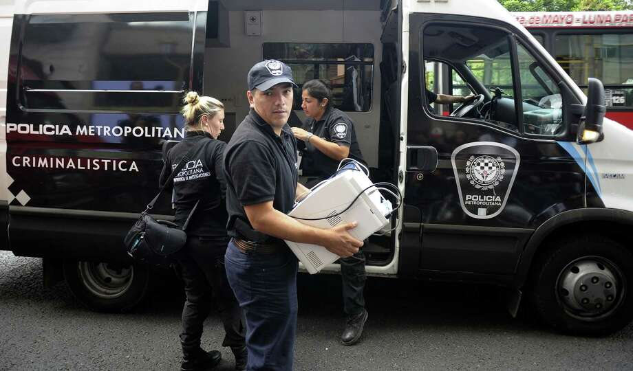 Members of the Metropolitan Police unload materials to make a raid at the offices of Argentine prosecutor Alberto Nisman in Buenos Aires on January 20, 2015 two days after he was found dead at his apartment. Amid a public uproar, President Cristina Kirchner's government pledged full backing Tuesday of a probe into the suspicious death of a prosecutor who had accused her of obstructing his investigation of the 1994 bombing of a Jewish community center. Alberto Nisman, 51, was found dead at his home Sunday from a gun shot to his temple in what authorities have said appeared to be a suicide the day before he was to present evidence against Kirchner at a congressional hearing.   AFP PHOTO / ALEJANDRO PAGNIALEJANDRO PAGNI/AFP/Getty Images Photo: ALEJANDRO PAGNI / AFP / Getty Images / AFP