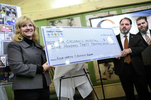 Pam DeMarco, left, her husband Don DeMarco, center, and their son Ryan DeMarco present a monetary gift to the Bernard & Millie Duker Children's Hospital through the Tyler DeMarco Foundation on Tuesday, Jan. 20, 2015, at Albany Medical Center in Albany, N.Y. DeMarco's son Tyler died in 2010 at age 12 from cancer. (Cindy Schultz / Times Union) Photo: Cindy Schultz / 00030258A