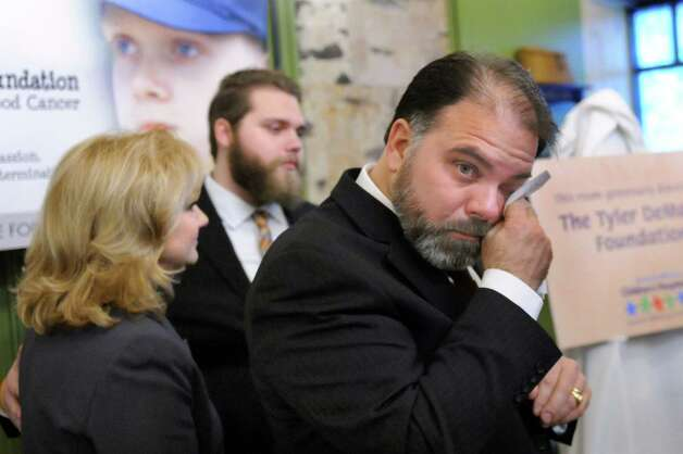 Don DeMarco, right, is filled with emotion when his family presents a monetary gift to the Bernard & Millie Duker Children's Hospital through the Tyler DeMarco Foundation on Tuesday, Jan. 20, 2015, at Albany Medical Center in Albany, N.Y. DeMarco's son Tyler died in 2010 at age 12 from cancer. Joining DeMarco are his wife, Pam DeMarco, left, and their son Ryan DeMarco. (Cindy Schultz / Times Union) Photo: Cindy Schultz / 00030258A