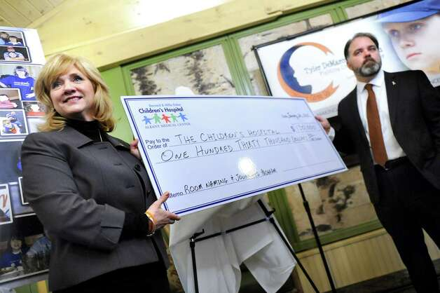 Pam DeMarco, left, her husband Don DeMarco present a monetary gift to the Bernard & Millie Duker Children's Hospital through the Tyler DeMarco Foundation on Tuesday, Jan. 20, 2015, at Albany Medical Center in Albany, N.Y. DeMarco's son Tyler died in 2010 at age 12 from cancer. (Cindy Schultz / Times Union) Photo: Cindy Schultz / 00030258A
