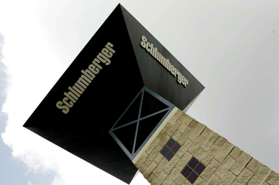 Schlumberger's logo towers over its campus in Sugar Land.  The world's largest oil field services company will report first-quarter earnings later this week amid an oil price collapse that already has cost thousands of jobs.   (AP Photo/Pat Sullivan, File) Photo: Pat Sullivan, STF / AP