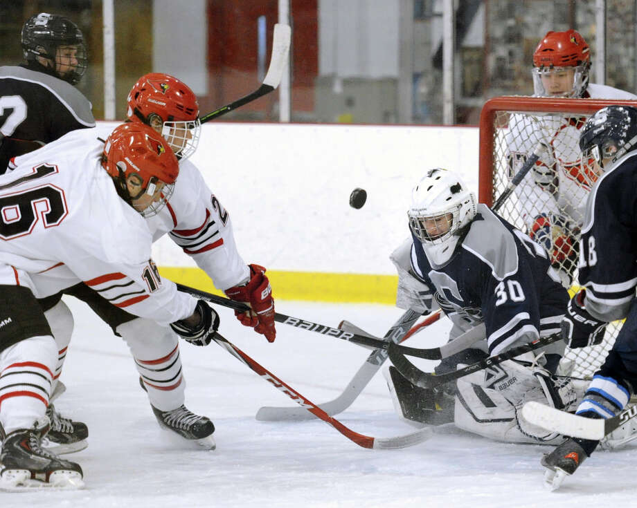 At left, Charlie Whiteley (#16) of Greenwich and teammate Kevin Piotrzkowski (#2), at center, go for a loose puck in front of  Staples-Weston-Shelton goalie Zachary Bloom, right, during the boys high school ice hockey game between Greenwich and the Staples-Weston-Shelton combined team at Hamill Rink, Greenwich Conn., Tuesday, Jan. 20, 2015. At right is Ryan Purgay (#18) of Staples-Weston-Shelton. Greenwich won the game, 8-3. Photo: Bob Luckey / Greenwich Time