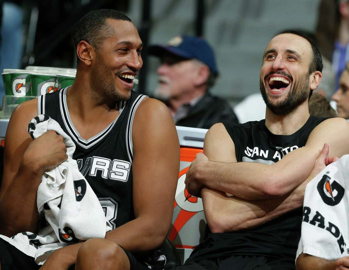Boris Diaw jokes with guard Manu Ginobili on the bench late in the fourth quarter of the Spurs' 109-99 win in Denver.