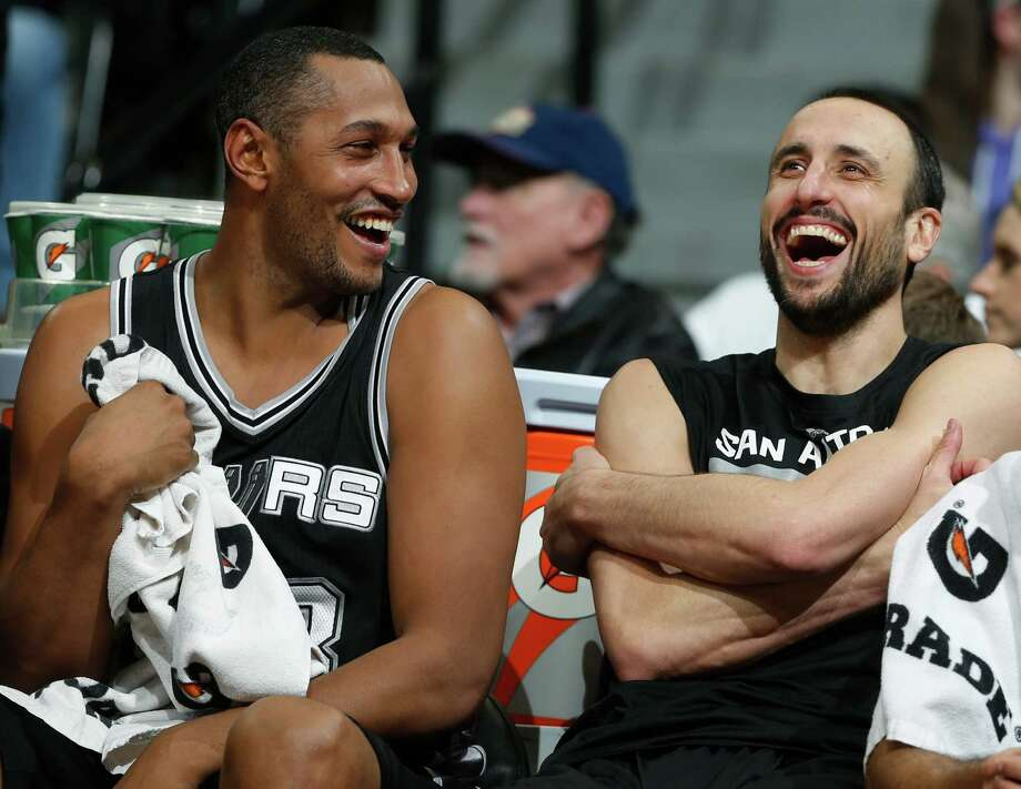 Boris Diaw jokes with guard Manu Ginobili on the bench late in the fourth quarter of the Spurs' 109-99 win in Denver. Photo: David Zalubowski /Associated Press / AP