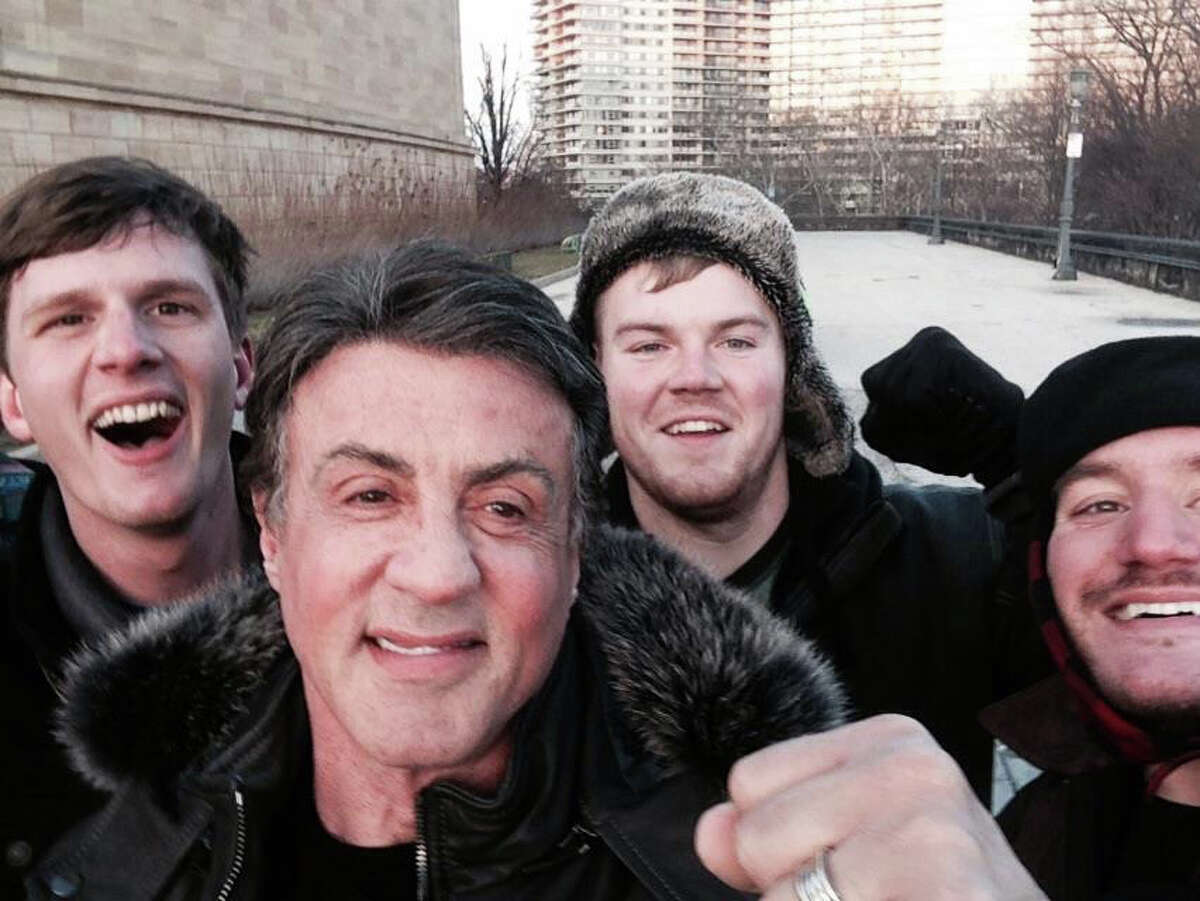 In this Jan. 17, 2015, photo provided by Peter Rowe, Rowe, right, takes a selfie with friends Jacob Kerstan, left, Andrew Wright, third from left and actor Sylvester Stallone in Philadelphia. Rowe said the three friends had just finished racing up the staircase at the city's Museum of Art when they saw Stallone. Stallone made the steps famous in his first turn as fictional boxer Rocky Balboa, who used them as part of his training regimen. Thousands of people now visit the steps each year to re-create the run.