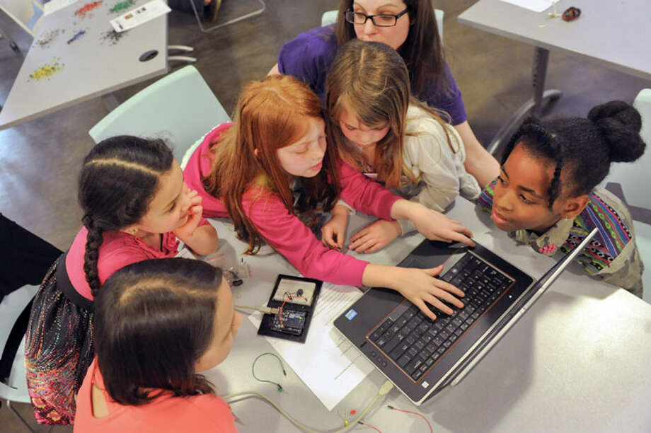 Girls put their heads together to program a song on a micro-controller device during Girls in STEM on Saturday, April 26, 2014, at TEC-SMART in Malta, N.Y. From left are Isabella Fredericksen, 11, of Ballston Spa, her sister Madeline Fredericksen, 7, Emerson Linthicum, 7, of Guilderland, her sister Maggie Linthicum, 5, and Amne Aurelie, 9, of Queens. Assisting the girls is volunteer Whitney Norris, top center. Photo: Cindy Schultz/Times Union Archive / 00026624A