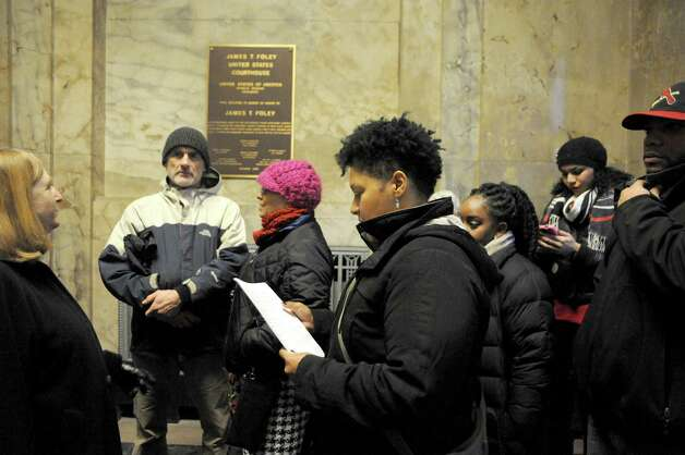 Angelica Clarke, center, of Troy looks over papers , concerning the handling of the killings of Michael Brown and Eric Garner, she and a group of activists were delivering to US Attorney's Office Northern District of New York in U.S. District Court on Friday Dec. 5, 2014 in Albany, N.Y.  (Michael P. Farrell/Times Union) Photo: Michael P. Farrell / 00029765A