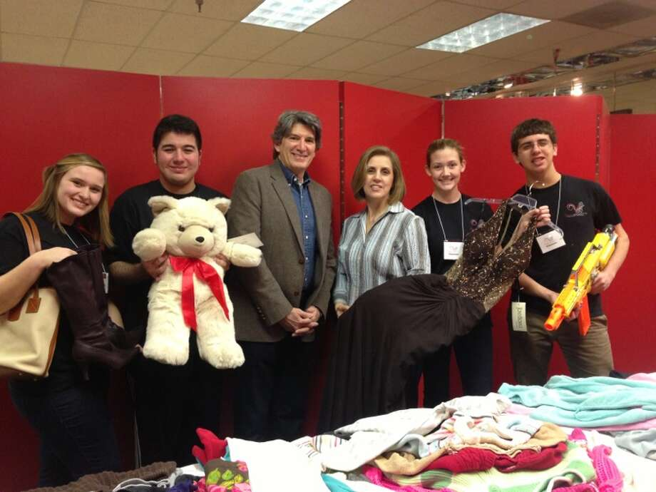 Virtuosi Chamber Orchestra members show off items for sale at their Jan. 17 Benefit Bazaar at Memorial City Mall to raise funds for a weeklong March trip to Paris to study and perform at the Conservatoire de Paris, an institution for young French musicians. From left are: Virtuosi members Madeline Keig and José Camacho; Harry Hadland, VP property management for MetroNational; Bazaar Coordinator Donna McNabb, and Virtuosi members Anna Emmick, and Jonathan McNabb. The total is to raise $37,501 to send 50 musicians ranging from ages 11 to 18 to Paris in March. To donate, supporters can visit http://kck.st/1vYHwkn. Photo: MetroNational