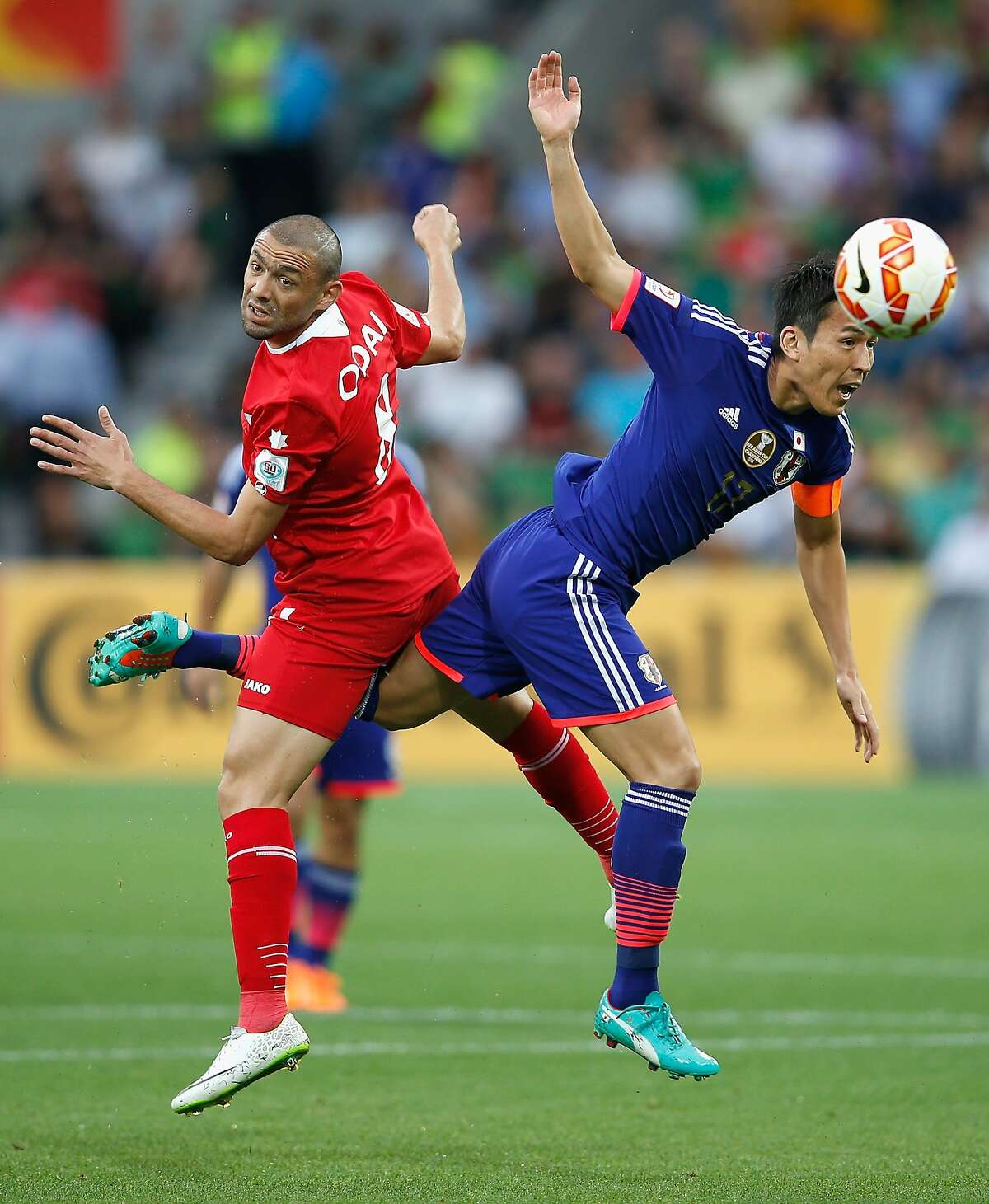 NOW KNOWN AS 'OCTAVE-HIGHER ODAI': Odai Al Saify of Jordan and Makoto Hasebe collide while going for the ball during an Asian Cup match between Japan and Jordan in Melbourne.