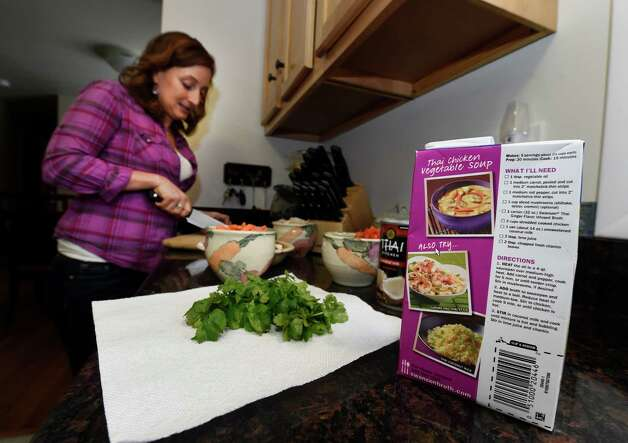 Carrie Bernardi prepares Thai chicken vegetable soup from a box Monday afternoon, Jan. 19, 2015, in Slingerlands, N.Y.     (Skip Dickstein/Times Union) Photo: SKIP DICKSTEIN / 00030243A