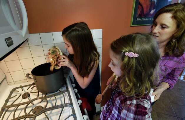 Taylor Ross, 11, left, and Auden Rapp, 8, center, assist Carrie Bernardi in the preparation of Thai chicken vegetable soup from a box Monday afternoon, Jan. 19, 2015, in Slingerlands, N.Y.     (Skip Dickstein/Times Union) Photo: SKIP DICKSTEIN / 00030243A