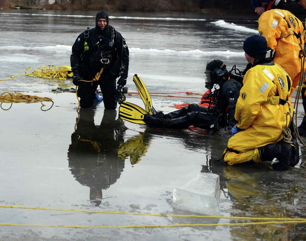 Battalion Chief Ron Wetmore sits on the ice as Firefighter Jason Dombrowski, right, is pulled from the water as the Milford Fire Department holds an ice diving drill in Mondo Ponds Wednesday, Jan. 21, 2015 behind John F. Kennedy School in Milford, Conn.
