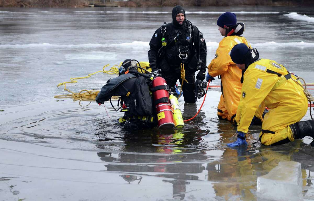 Milford Firefighter Zak Daniel enters the water in Mondo Pond as during an ice diving drill Wednesday, Jan. 21, 2015 in the frozen ponds behind John F. Kennedy School in Milford, Conn.