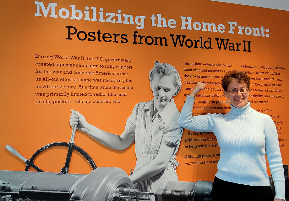 "Elizabeth Rose, the library director at the Fairfield Museum and History Center, strikes a Rosie the Riveter pose next to a sign promoting the museum's new exhibit, ""Mobilizing the Home Front: Posters from World War II."" Photo: Mike Lauterborn / Fairfield Citizen"