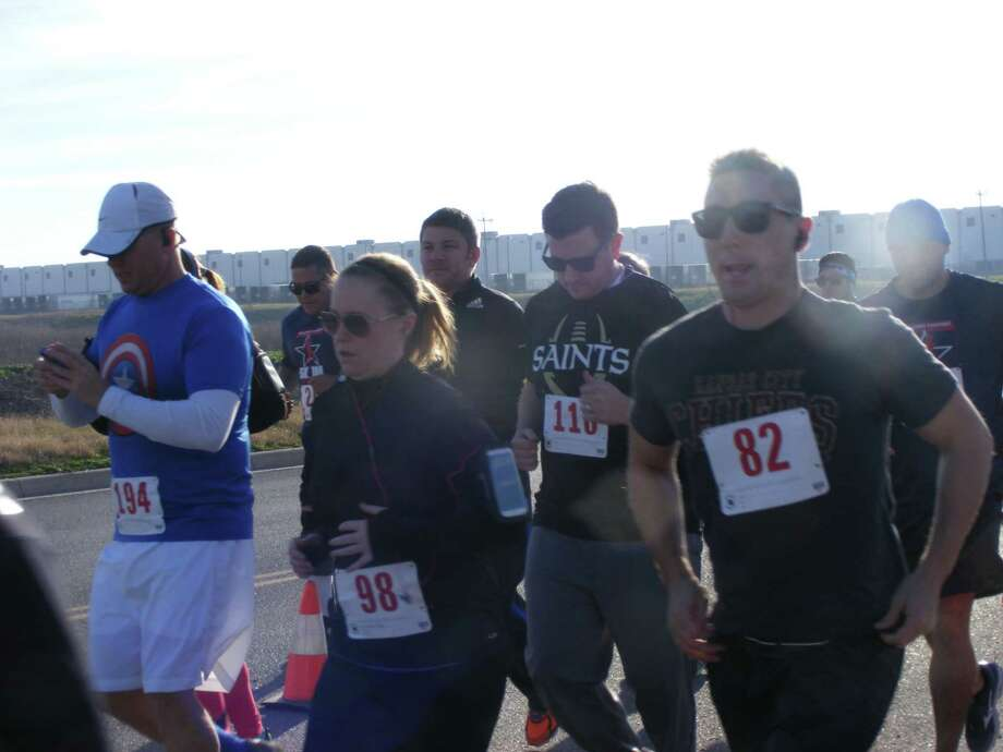 Runners Jon Short (194), Kathleen Karr (98), Ryan Leland (110) and Cameron Harms (82) leave the starting line in the Saturday, Jan. 17, Salute to Servicemembers 10K/5K run-walk at the Bluebonnet Palace in Selma. Photo: /David DeKunder / Northeast Herald