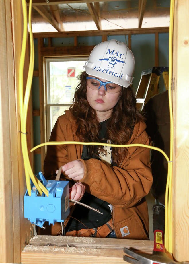 Dallas Hart, 17, pulls wires into a circuit box as forty stendents from MacArthur High School's  Electrical Systems Technology Technical Apprentice Program installed electrical wiring in four new Habitat for Humanity homes in the 1100 block of Gutierrez St. on Wednesday, Jan. 14, 2015.  The program, in its seventh year, gives students an opportunity to apply the knowledge they have learned in their electrial classes to a real world scenario, while at the same time giving back to the community.  MARVIN PFEIFFER/ mpfeiffer@express-news.net Photo: Marvin Pfeiffer, Staff / San Antonio Express-News / Express-News 2015