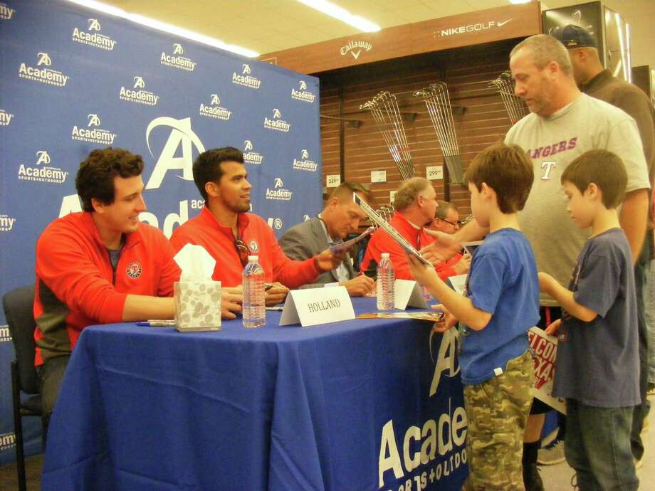 Texas Rangers catcher Robinson Chirinos (seated second from left) hands an autographed photo to Mark Wischert (right) during the Friday, Jan. 16, appearance of the Texas Rangers Winter Caravan stop at Academy Sports + Outdoors in Selma. Rangers pitcher Derek Holland (far left) signs autographs for (standing, left) Carson and Joshua Wischert. Photo: David DeKunder / Northeast Heral