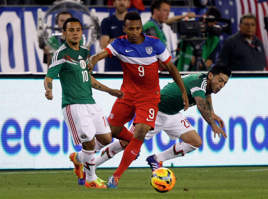 U.S. Julian Green (9) battles for the ball with Mexico defenders during a friendly soccer match in April 2014 in Glendale, Ariz. The game ended in a 2-2 draw. There will be a friendly rematch in San Antonio on April 15. Photo: Rick Scuteri /Associated Press / FR157181 AP