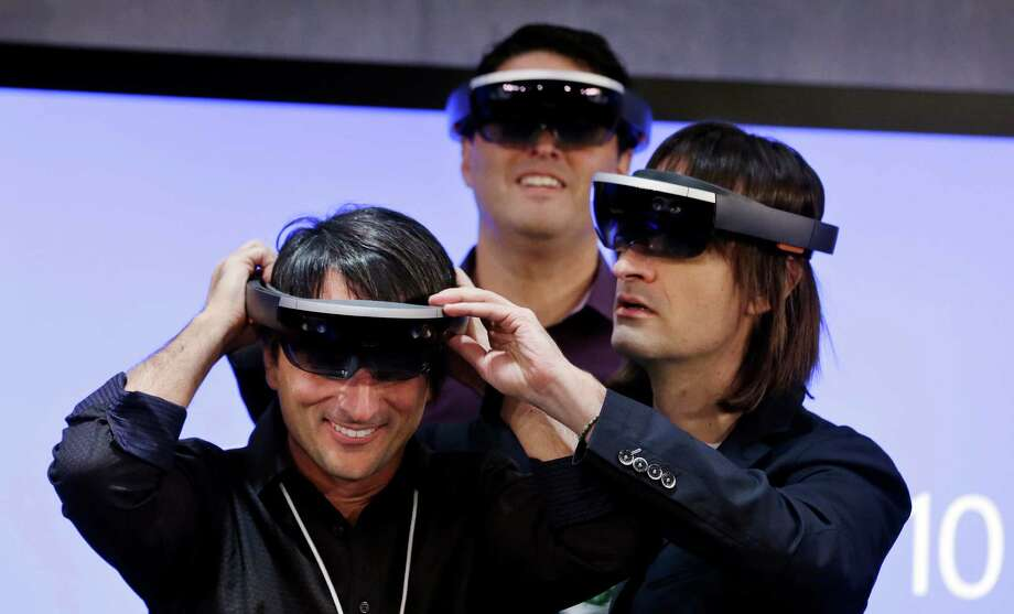 "Microsoft's Joe Belfiore, left, smiles as he tries on a ""Hololens"" device with colleagues Alex Kipman, right, and Terry Myerson following an event demonstrating new features of Windows 10 at the company's headquarters on Wednesday, Jan. 21, 2015, in Redmond, Wash. Executives demonstrated how they said the new Windows is designed to provide a more consistent experience and a common platform for software apps on different devices, from personal computers to tablets, smartphones and even the company's Xbox gaming console. (AP Photo/Elaine Thompson) ORG XMIT: WAET109 Photo: Elaine Thompson / AP"