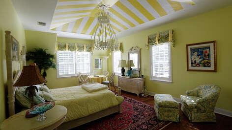 The Palm Beach guest bedroom on the second floor is painted in yellow at the home of Kirk Mills in Terrill Hills.