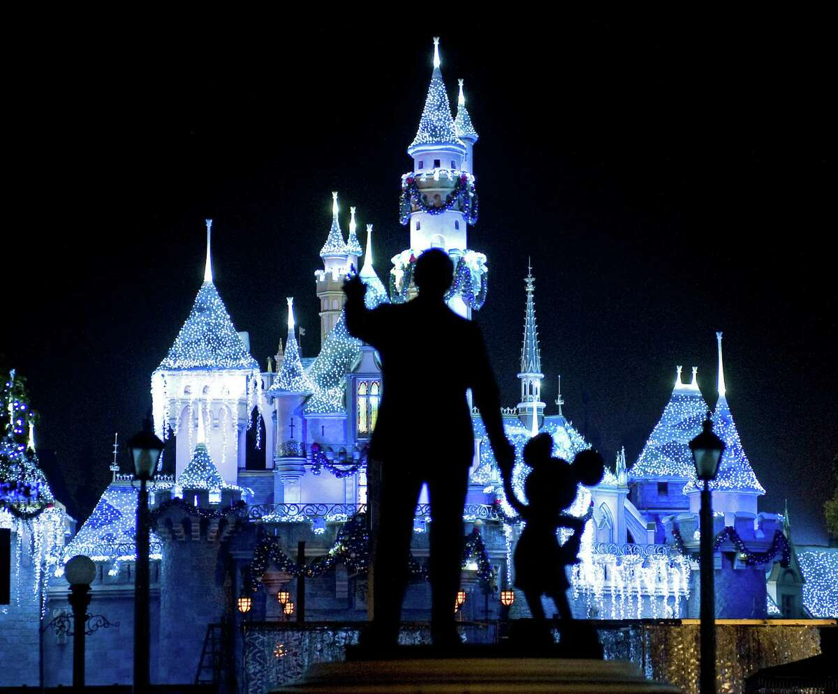 """This Nov. 20, 2009 photo shows Sleeping Beauty's Castle in winter dress with the iconic """"Partners"""" statue featuring images of Walt Disney and Mickey Mouse in the foreground, at Disneyland in Anaheim, Calif. Measles cases have been popping up around California in an outbreak linked to visits to Disneyland and Disney's California Adventure theme parks during the winter 2014 holiday. The highly contagious respiratory illness was declared eliminated in the U.S. in 2000, but health officials have seen a surge of measles infections in the country in recent years."""