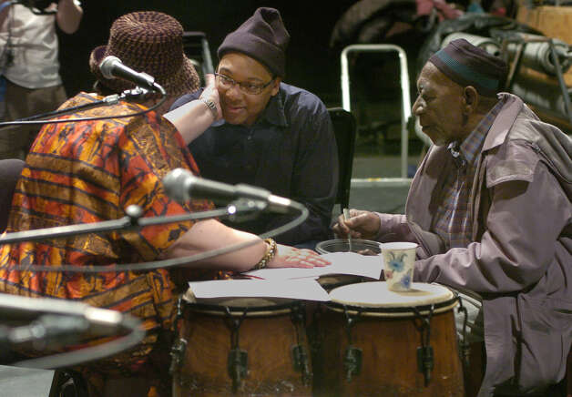"""Times Union staff photo by Paul Buckowski    Amina Addy, left, manager of the African dance and drum ensemble Odadaa, reaches out to musician Wynton Marsalis, center, as Marsalis talked with Amina and her husband and founder and leader of the drum ensemble, Yacub Addy, right, as they began to work on their second collaboration while rehearsing at the Hart Theater at The Egg in Albany, N.Y. on Thursday, Jan. 5, 2006.  The collaborative work, entitled, """"Congo Square"""" will be performed in the spring of this year. Photo: Paul Buckowski / Albany Times Union"""