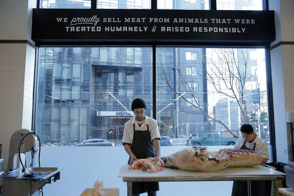 Rachel Denning and JT Sagundes, left, butcher a side of beef at The Market, a new marketplace on Market Street on the ground floor of the Twitter building in San Francisco, Calif., on Tuesday, January 20, 2015. It is divided into different areas: grocery, meat, fish, flowers, etc.