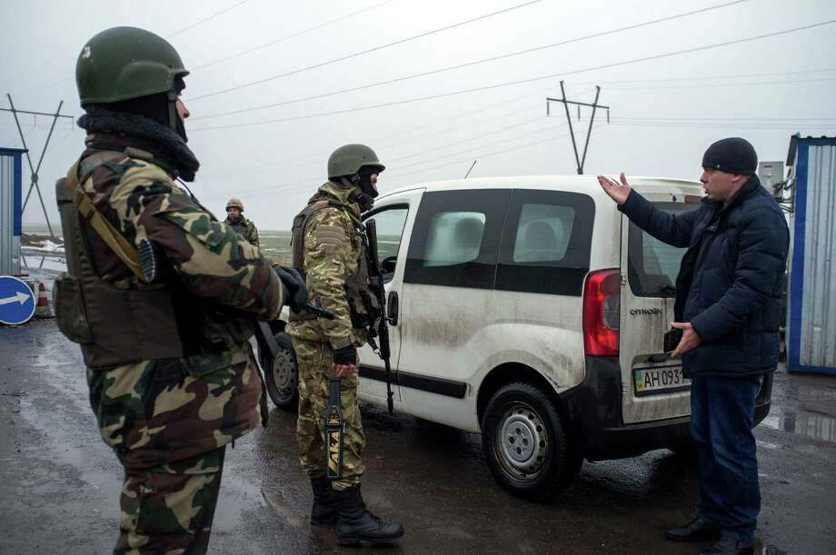 Ukrainian forces servicemen check passengers of a car at a checkpoint in the eastern Ukrainian city of Kurakhove, near Donetsk on January 21, 2015. Heavy fighting raged between Ukrainian forces and pro-Russian rebels in the country's war-torn east Wednesday, killing at least five more civilians ahead of high-stakes peace talks in Berlin. AFP PHOTO/ OLEKSANDR STASHEVSKIYOleksandr Stashevskiy/AFP/Getty Images Photo: OLEKSANDR STASHEVSKIY / AFP