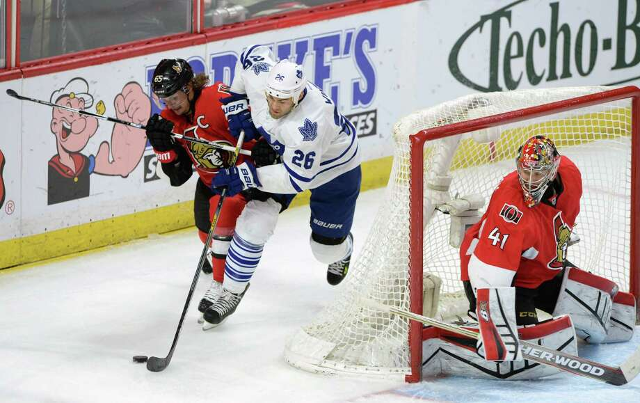 Ottawa Senators' Erik Karlsson, left, fights to push Toronto Maple Leafs' Daniel Winnik off the puck as Sens goalie Craig Anderson keeps an eye out during second period NHL hockey action in Ottawa, Ontario, on Wednesday, Jan 21, 2015. (AP Photo/The Canadian Press, Sean Kilpatrick) ORG XMIT: OTTK108 Photo: Sean Kilpatrick / CP