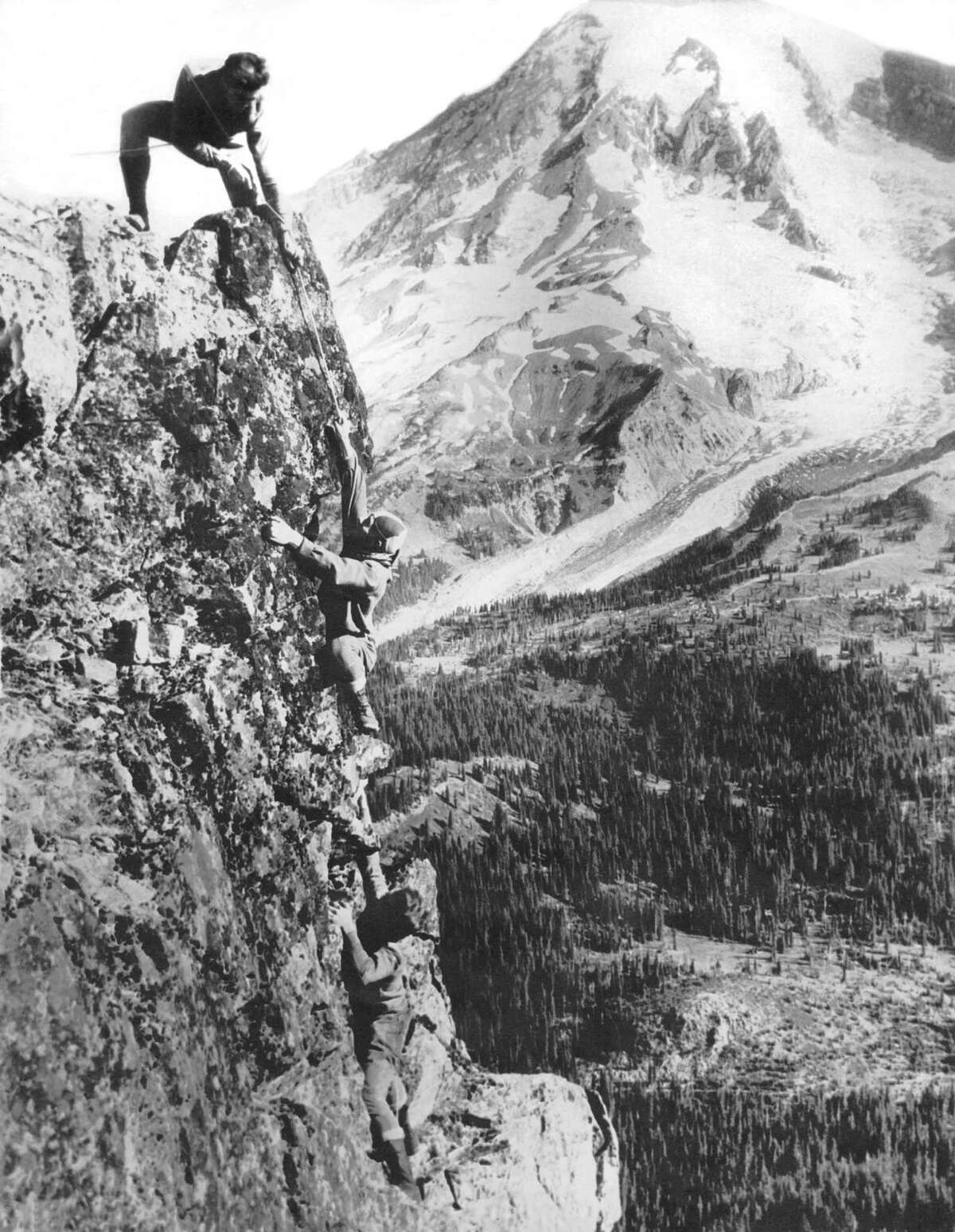 A party of three mountain climbers just as they are about to reach the top of Pinnacle Peak overlooking Paradise Valley, Mount Rainier National Park, Washington, August 15, 1925.