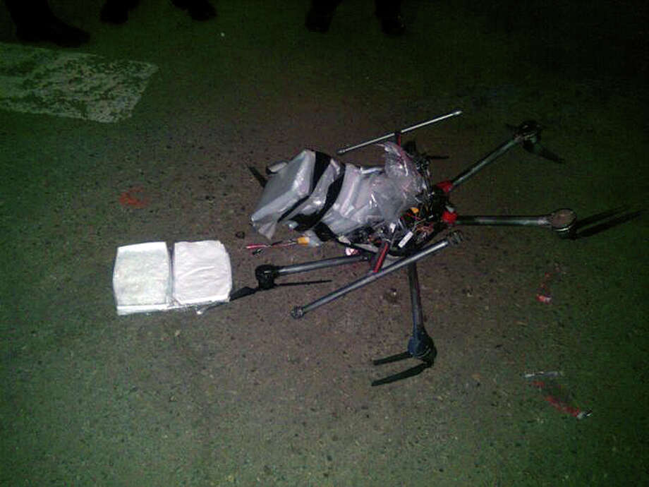 In this image released by the Tijuana Municipal Police on Wednesday Jan. 21, 2015, a drone loaded with packages containing methamphetamine lies on the ground after it crashed into a supermarket parking lot in the city of Tijuana on Tuesday Jan. 20, 2015. According to police, six packets of the drug, weighing more than six pounds, were taped to the six-propeller remote-controlled aircraft. Authorities are investigating where the flight originated and who was controlling it. He said it was not the first time they had seen drones used for smuggling drugs across the border. Other innovative efforts have included catapults, ultralight aircraft and tunnels. Photo: Secretaria De Seguridad Pública Municipal De Tijuana, AP / Secretaria de Seguridad Pública Municipal de Tijuana