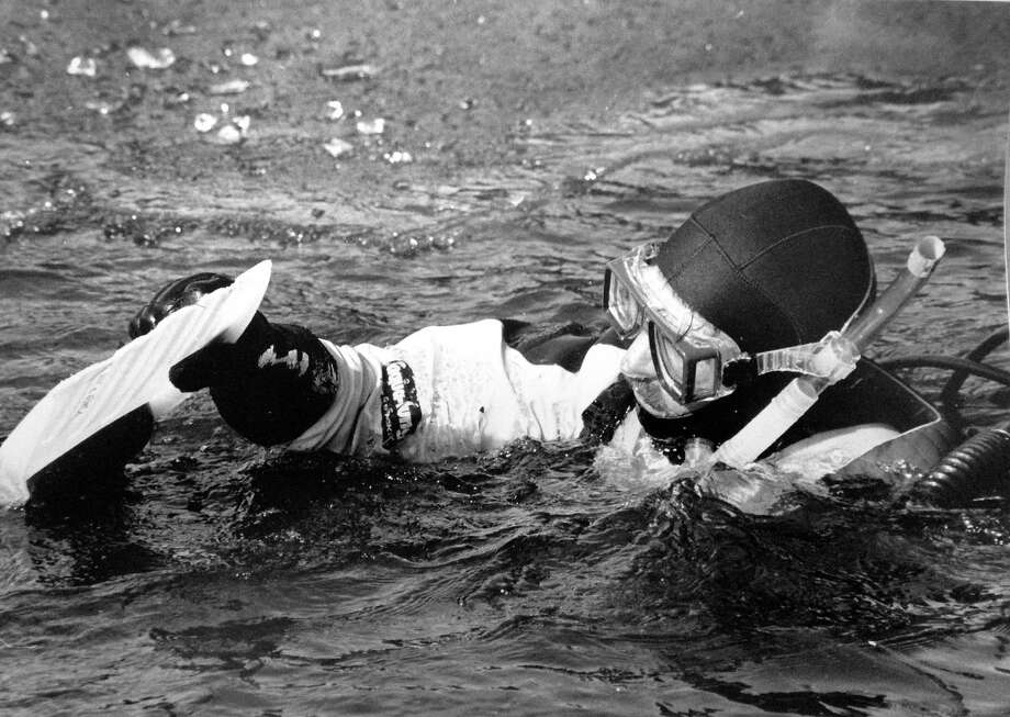 Stamford Fire & Rescue Department Lt. Mark Roche takes off his fins after a SCUBA swim under the ice at the North Stamford Reservoir on Lakeside Drive during a drill on Jan. 30, 1990. Photo: File Photo/Tom Ryan / Stamford Advocate File Photo