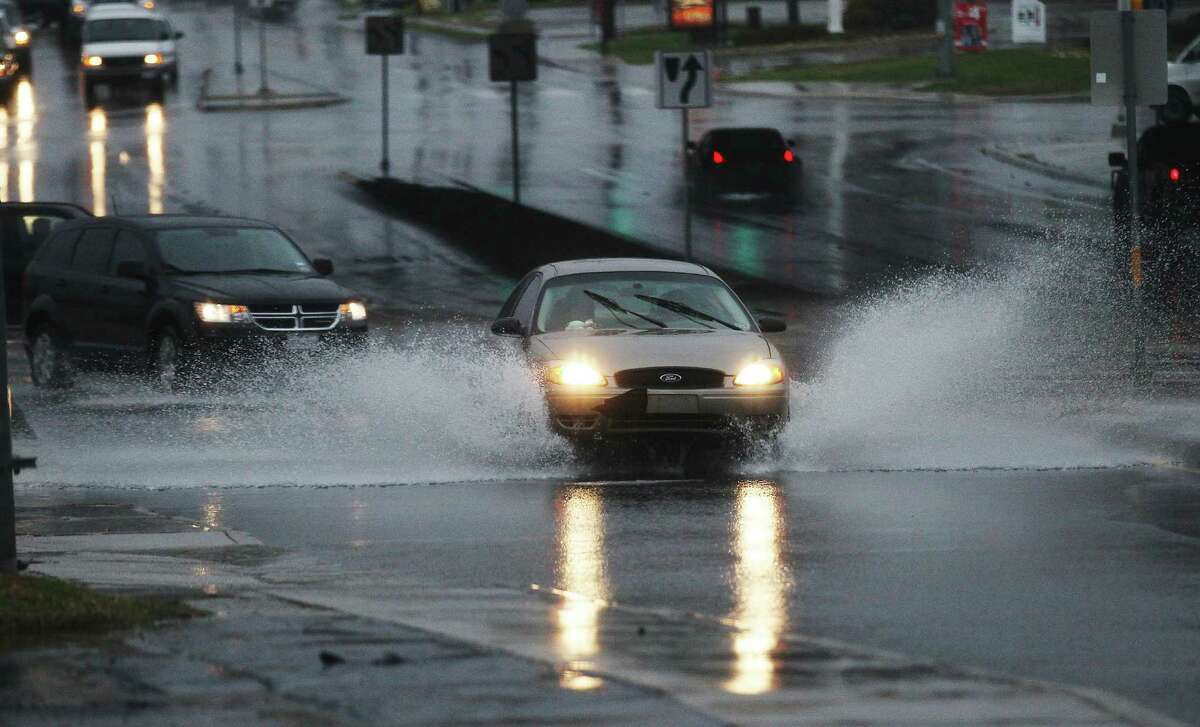 Motorists drive through pools of rain water near West Avenue and IH-10 on Thursday, Jan. 22, 2015.