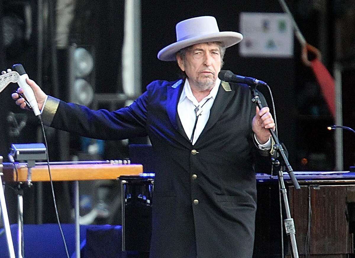 """FILE - This July 22, 2012 file photo shows U.S. singer-songwriter Bob Dylan performing on stage at """"Les Vieilles Charrues"""" Festival in Carhaix, western France. The icon is on the cover of AARP magazine's February/March 2015 issue. He says in the interview that """"if I had to do it all over again, I'd be a schoolteacher."""" (AP Photo/David Vincent, file)"""