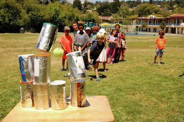 "Kids knock over cans during the ""wacky creative arts"" week at the Education Française Bay Area's summer camp. Camps are held in Berkeley, Mountain View, San Francisco and Santa Rosa."