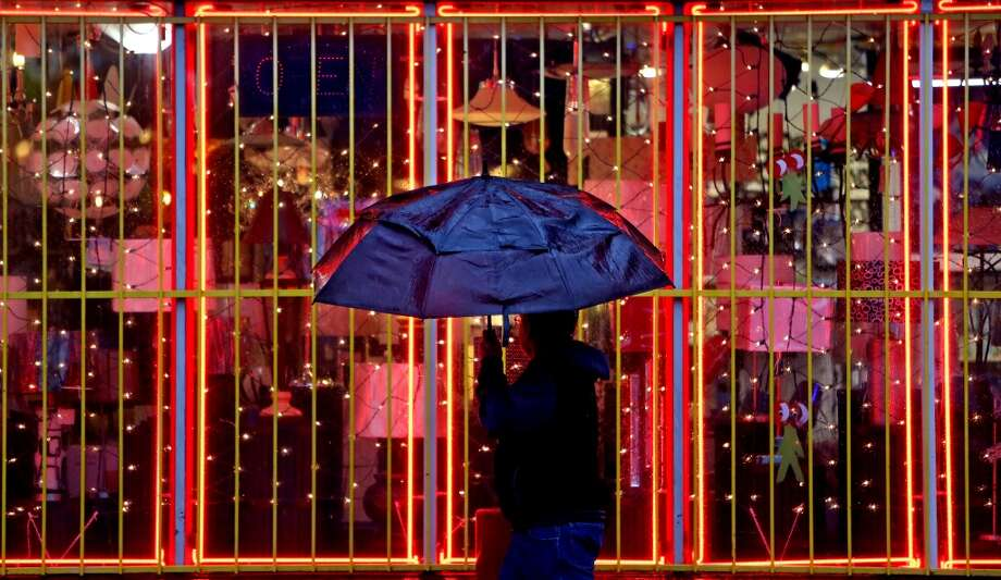 A pedestrian walks past Light Bulbs Unlimited during a rain shower along Westheimer Road on Thursday, Jan. 22. Photo: Gary Coronado, Houston Chronicle