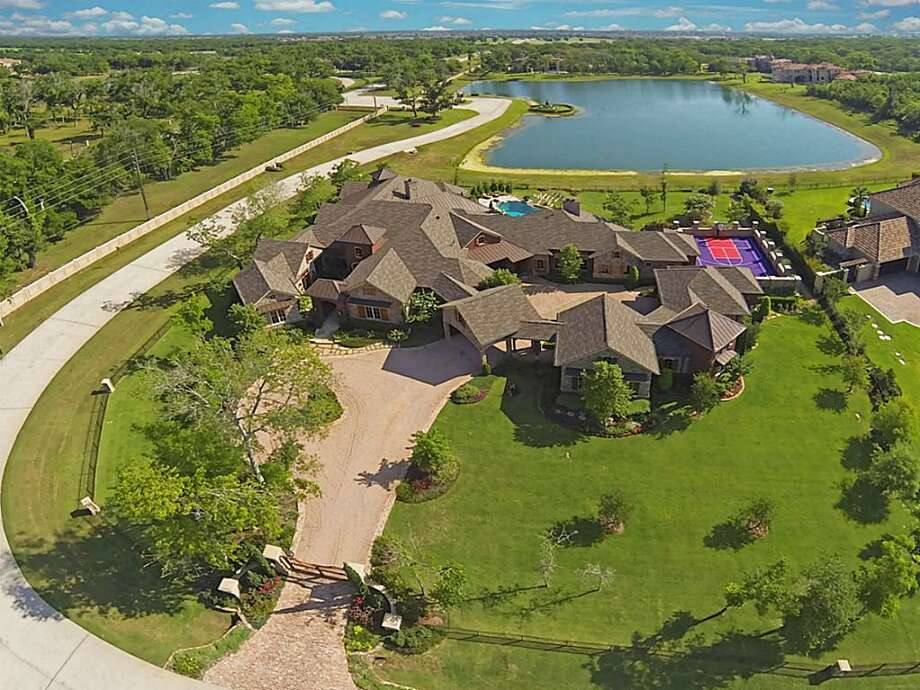 10 Retreat Blvd: This waterfront estate is packed with notable features such as brick and stonework throughout, a purple athletic court, sparkling lakefront pool and hot tub, and an over-sized outdoor chess area. Photo: Courtesy Of Houston Association Of Realtors