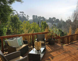 The deck overlooking the yard offers a wooden railing and areas for gathering and planting.