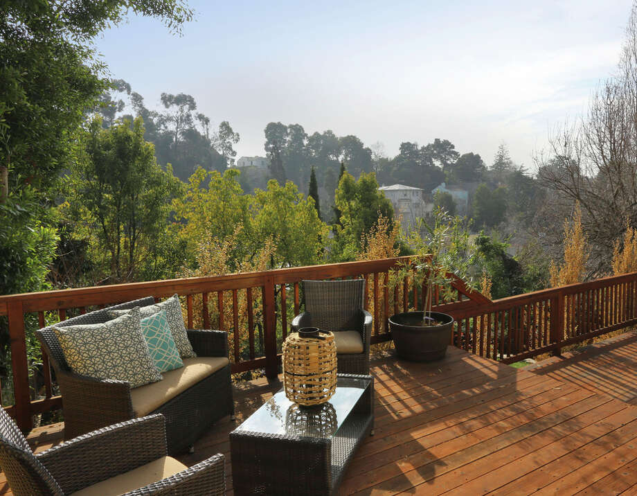The deck overlooking the yard offers a wooden railing and areas for gathering and planting. Photo: Liz Rusby/Grubb Co. / ONLINE_CHECK